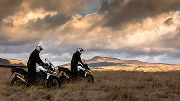 Two Triumph riders in a meadow with sun setting in the background
