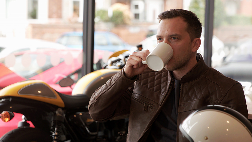 Man drinking coffee in Triumph dealership