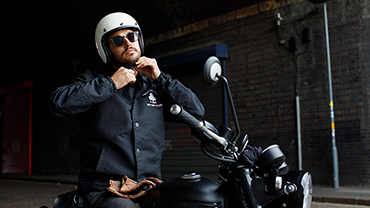 Male model wearing Triumph x Ace Cafe Collection putting helmet on