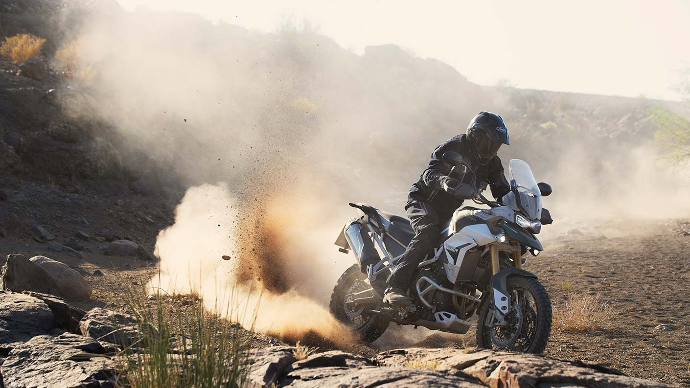 Off road riding shot of a Triumph Tiger 900 Rally Pro kicking up a cloud of dust