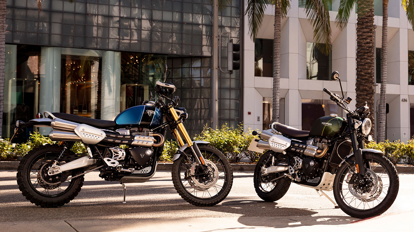 Two Triumph Scrambler 1200s parked in urban area, with sunlight highlighting iconic modern classic styling