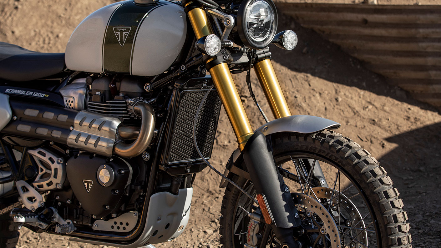 Triumph Scrambler 1200 XE stationary with sunlight illuminating gold front forks, sculpted exhaust and Triumph badging