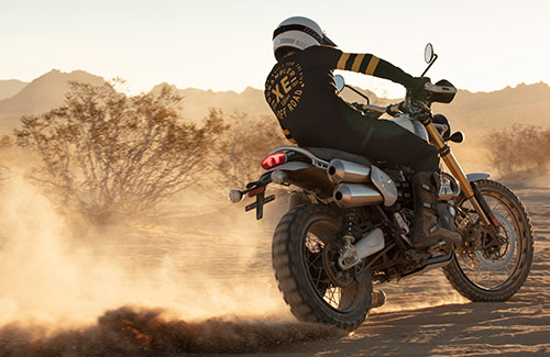 Innovative Triumph Scrambler 1200 scrambling along a salt flat in thrilling style, with the rider wearing the limited edition Scrambler 1200 clothing collection and Triumph dirt boots