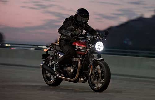 All-new Triumph Speed Twin riding through at dusk  across flat urban road