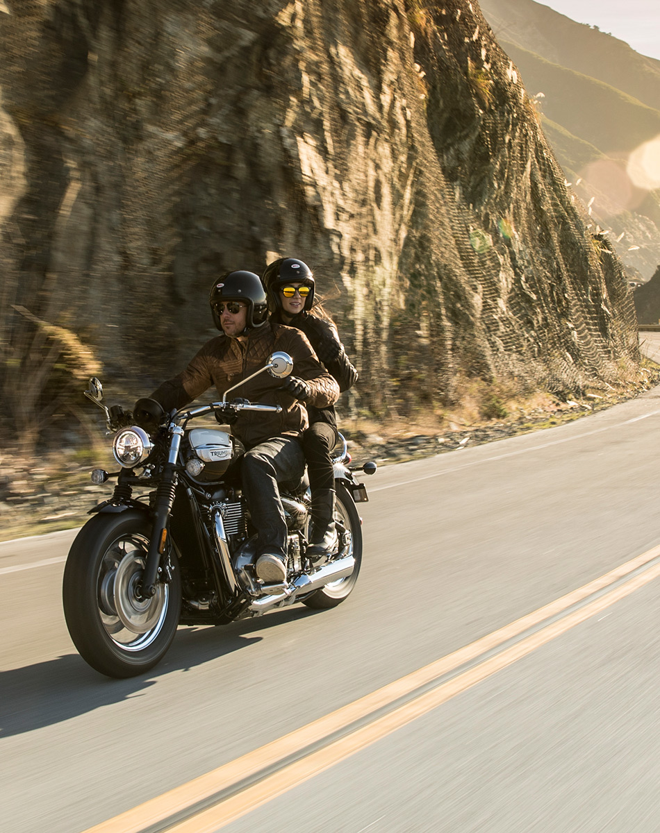 Man and woman riding Triumph Bonneville Speedmaster on road